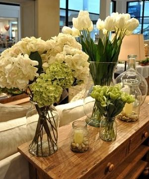 The white flowers create an elegant feel. Clear vases lighten the look for Spring!