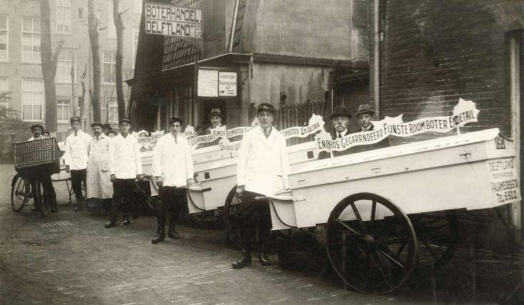 Bezorgers van boterhandel Delftland in witte jassen bij hun handkarren, gereed om boter te gaan bezorgen. Nederland, Amsterdam, 1920.