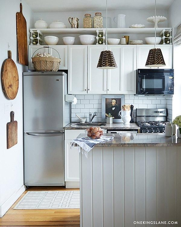 Small all-white kitchen with wood accents, open shelves and vertical storage.