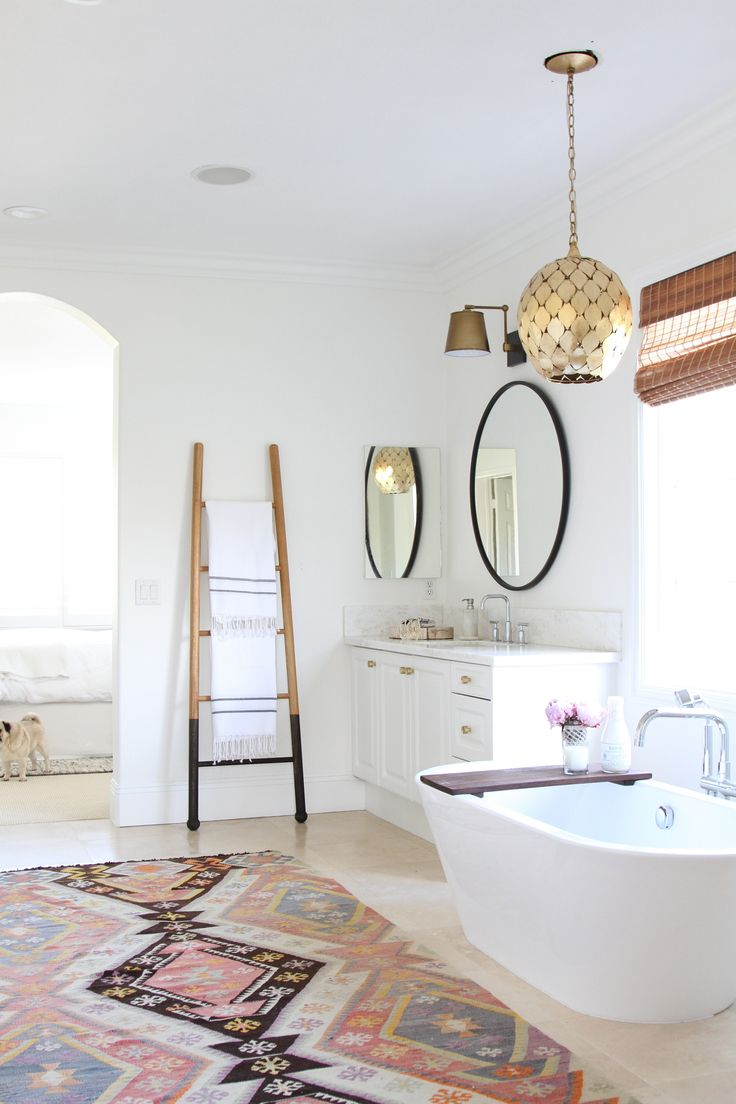 "Forget a little bath mat. You can't go wrong with a large, vibrant rug in a serene white bathroom, says Owens. ""I like to decorate with a clean, minimal palette, leaving room for accessories that individualize and make the space."" This graphic kilim brings energy without disturbing the peace."