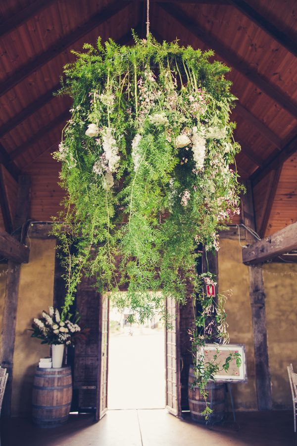 A foliage installation (our chandelier) of fern, jasmin, stock, roses, and queen anne's lace, hung above the bridal table at the wedding venue reception, and looked incredible!