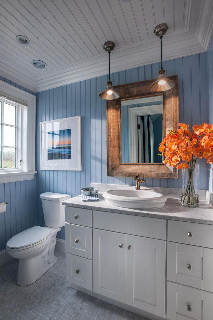 A locally-framed photograph of a Martha's Vineyard sunset successfully unifies the soothing blue and warm orange accents in this serene guest bathroom retreat.