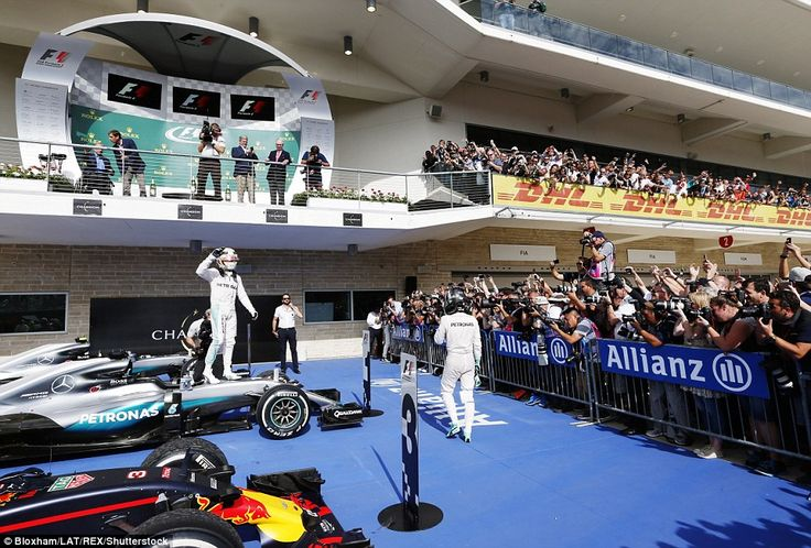 Hamilton stands on top of his car to celebrate victory as Rosberg trudges past having finished second behind his team-mate