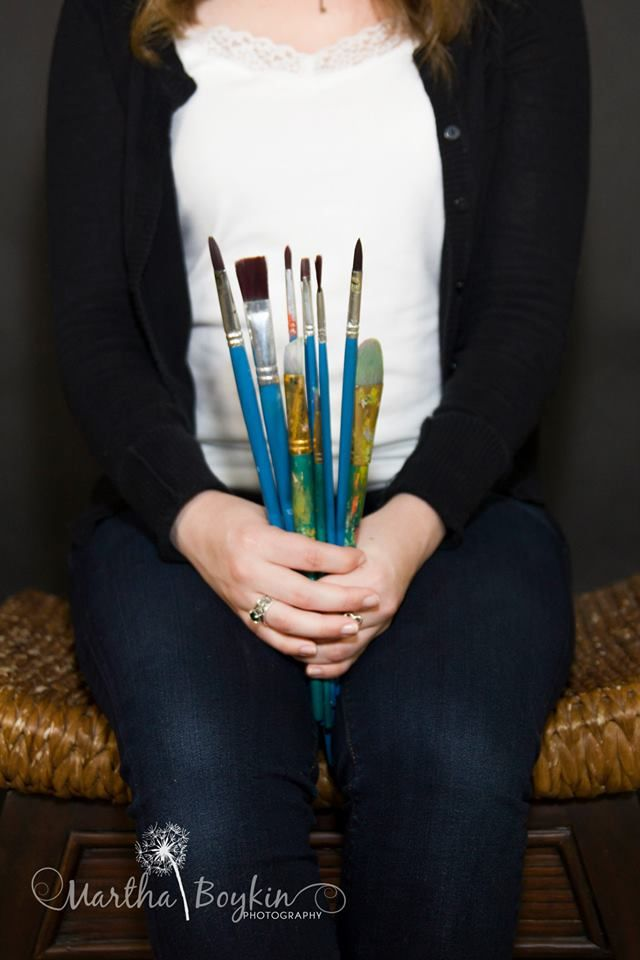for Kylie- colored pencils instead of paintbrushes, and a sketchbook (maybe with a drawing in progress) on her lap or beside her. But actually show her face in the picture too.