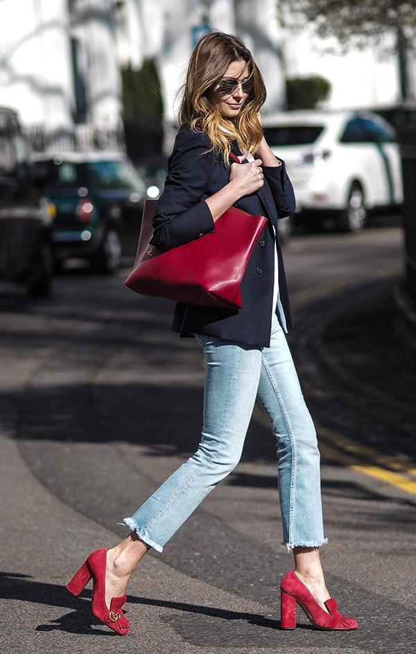 Emma Hill usa blazer azul marinho, calça jeans cropped, sapato vermelho gucci e bolsa vermelha