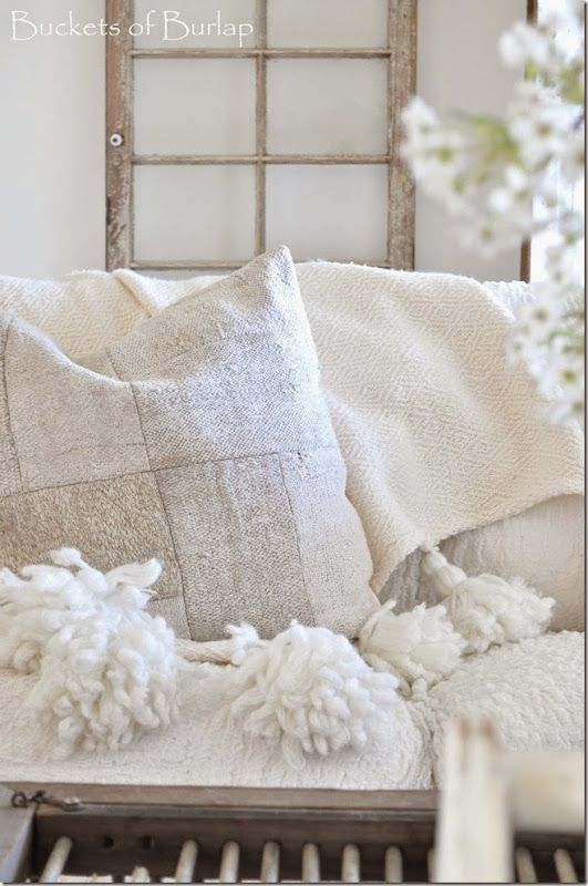 Vintage Country Farmhouse. Tassel Anthropologie throw, hemp patchwork pillow, white sofa, pear blossoms, crate coffee table, raw wood. Buckets of Burlap home and blog