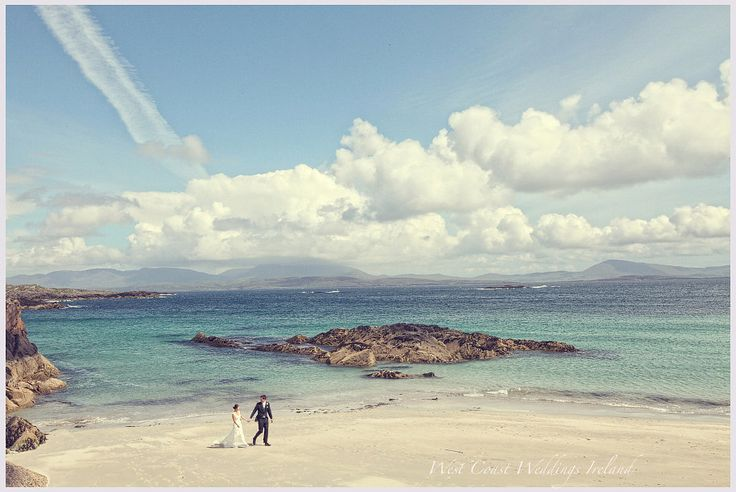 Couple walking on the beach with a beautiful blue sky and sea behind them
