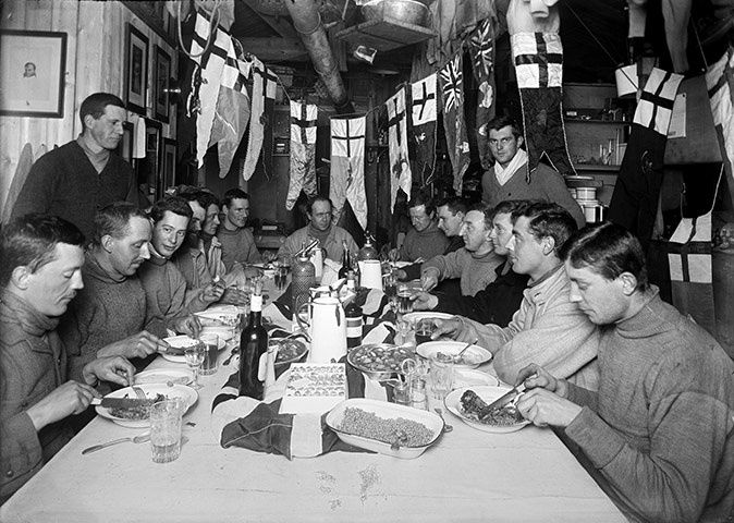 Captain Scott and members of the Terra Nova expedition celebrate his 43rd birthday at camp in the Ross Dependency of Antarctica, during his Terra Nova Expedition to the Antarctic, 6th June 1911. Scott is at the head of the table.  Photograph: Herbert Ponting/Scott Polar Research Institute