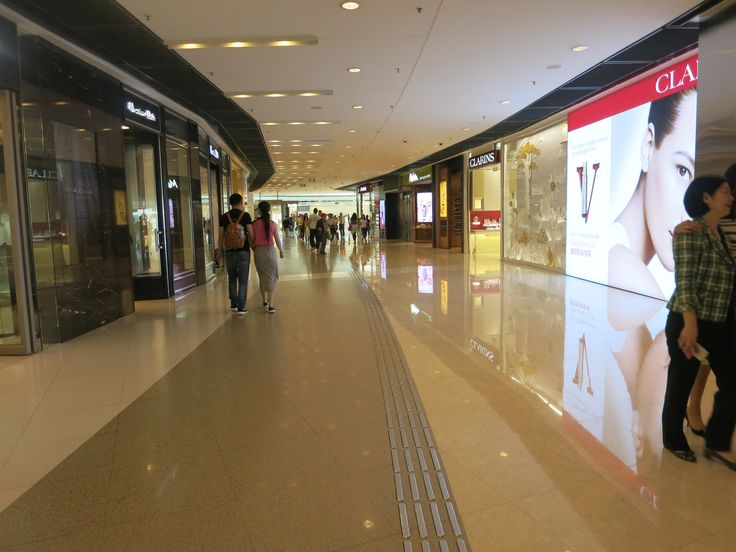 view of a shiny, clean and relatively empty hallway in an upscale shopping mall in Hong Kong