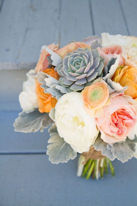 The bridal bouquet will be white hydrangeas, ivory garden roses, peach dahlias, white heather, gray brunia, jana spray roses, gray dusty miller, and gray succulents wrapped in ivory ribbon with brooch accents and the stems showing.