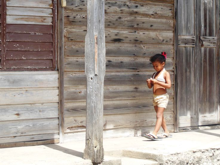 Near Baracoa's waterfront, I loved walking along this strip of weathered buildings. The texture, mellow colour and obvious age sang like the blues. Then this intense little girl came walking along to capture a photograph of memories. Photo by Kathryn MacDonald©