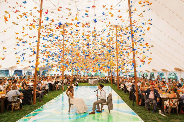 """Paper Butterflies - Breathtaking Ceiling Decoration IdeasFor Your Wedding - Southernliving. """"Thousands of colorful paper butterflies hung over a custom dance floor for this stunning daytime wedding,"""" explains Leahy, of this beautiful installation by Sillapere. """"The groom surprised the bride with a special song on the ukulele and the butterflies softly swayed in the breeze overhead."""""""