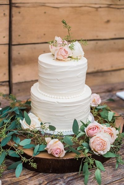 Elegant wedding cake idea - two-tier, buttercream-frosted wedding cake with blush flower topper + tree slice cake stand {Andrea Hallgren Photography}