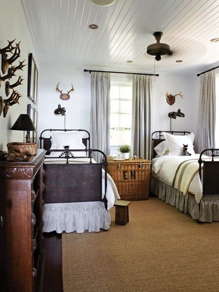 a ceiling antlers on the wall and a wicker trunk used as a bedside table give this room a look
