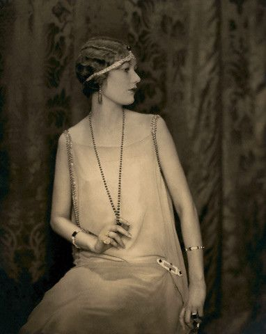 ca. 1924 --- Alden Gay wearing an emerald and pearl necklace; pear-shaped emerald earrings; a diamond and emerald cabochon headband; bracelets of diamonds, emeralds, and sapphires; a square emerald ring; an oblong pin of pave diamonds and square emeralds; and a large white diamond ring, all by Cartier