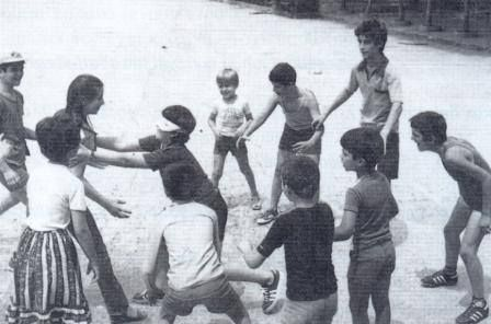 Families spread out elaborate picnics and play blind man's buff ; Τυφλόμυγα