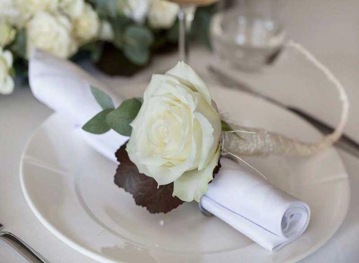 Hvit rose med pynt av grønne blader er stilig til kuvert
