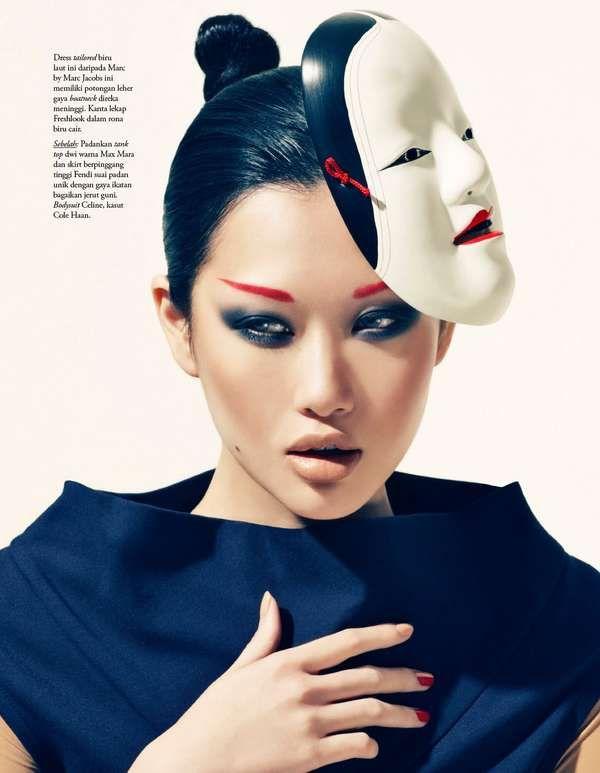 Glam Malaysia May 2010. Dark smokey eyes and red eyebrows on a beautiful Asian model wearing a kabuki style mask.