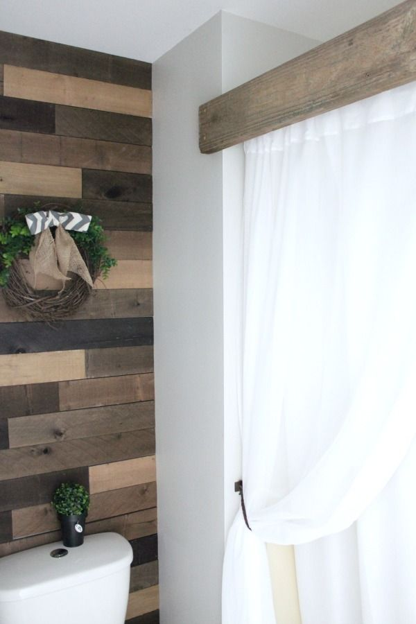 A unique way to frame in your dated shower insert. Use Pallet wood and a piece of scrap deck board to transform your dated space.