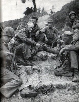 Ernie Pyle in Okinawa shares his cigarettes with some 1st Division marines as they rest at an Okinawa roadside.Pyle more than any writer told the story of the common G.I. A few days after this picture Pyle was killed.
