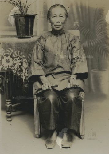 穿大襟衫梳客家高頭的婦人在吳金淼寫真館的攝影棚內照相