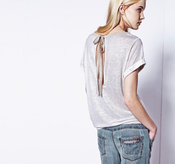 Cieniutki t-shirt z subtelnym dekoltem na plecach i luźne, jeansowe spodnie.