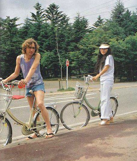 John Lennon and Yoko Ono ride bikes.