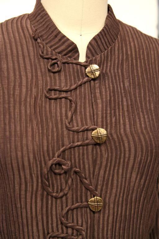 Van de stof is een bandje gemaakt wat decoratief op de blouse is genaaid. Door met het band lusjes aan de voorkant te maken, kunnen ze als sluiting worden gebruikt met de knopen.