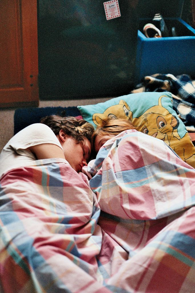 Cute couple sleeping close with lion king pillow and old checked blanket