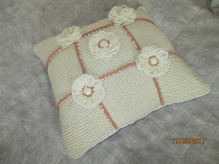 Langantähteistä neulottu sohvatyyny koristeltu lankakukkasin