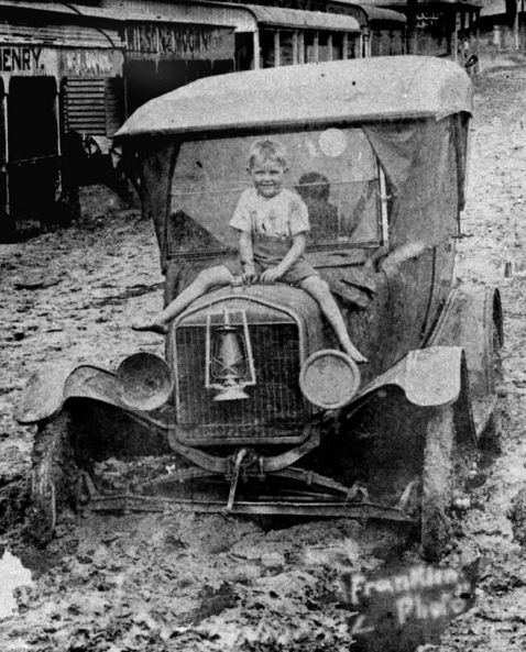 +~+~ Vintage Photograph ~+~+  Boy sitting on the bonnet of a car bogged down in mud from the 1925 flood at Innisfail, Queensland.