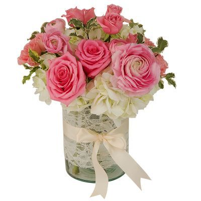 Dainty Lace - Pretty pink ranunculus and roses with cream hydrangea. The glass cylinder vase is wrapped with lace and tied with a satin ribbon.