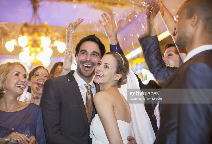 Stock Photo : Friends throwing confetti over bride and groom at wedding reception
