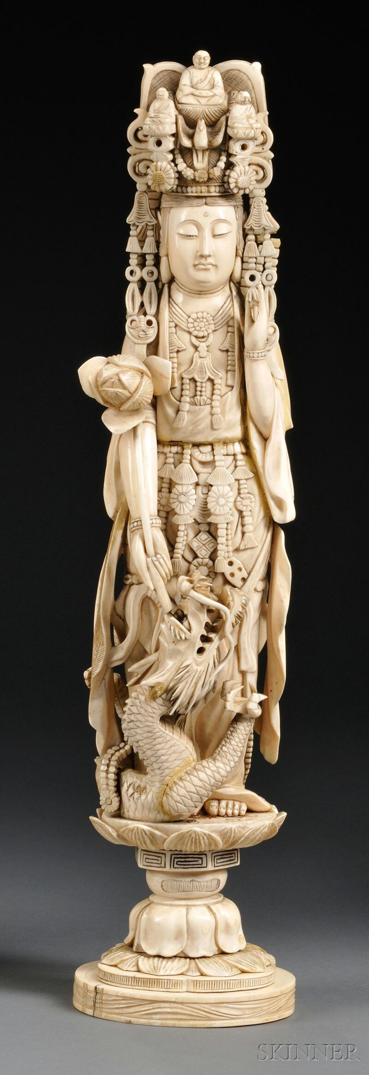 Ivory Carving of Kuan Yin with her left hand in the mudra of appeasement position, right hand holding a lotus blossom, a swirling dragon at feet, standing on a lotus base. China 19th Century
