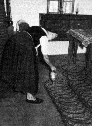 Döngölt földpadlójú szoba fellocsolása bádog locsolóval
