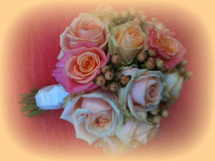 bridal bouquet with miss piggy roses, pearl and peach avalanche roses with mellow peach hypericum berries.