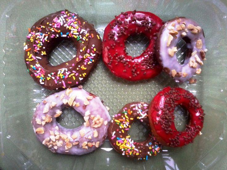 Donas y Mini Donas glaseadas de Chocolate con Chispas de Colores, Glaseado Blanco con Maní y Glaseado Rojo con Chispas de Chocolate.