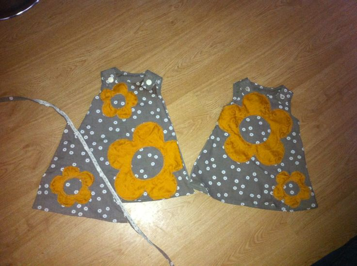 Picture of 2 little girls dresses hand made with flower appliqué and buttons, pictured with an optional bandana x