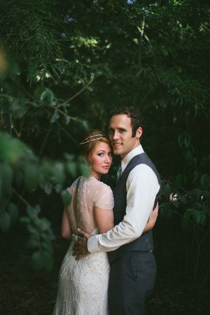 Groom and bride standing in forest looking at the camera @myweddingdotcom