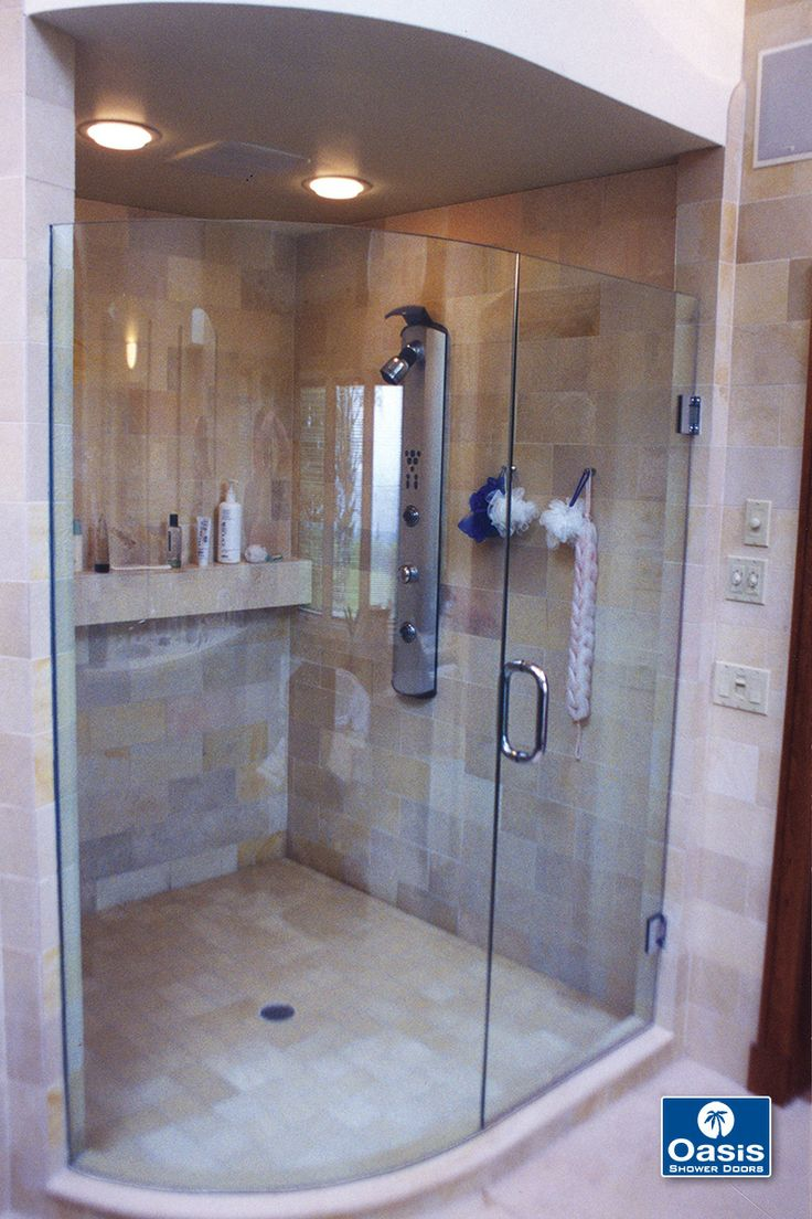 frameless shower door features curved fixed panel and wall mount hinges