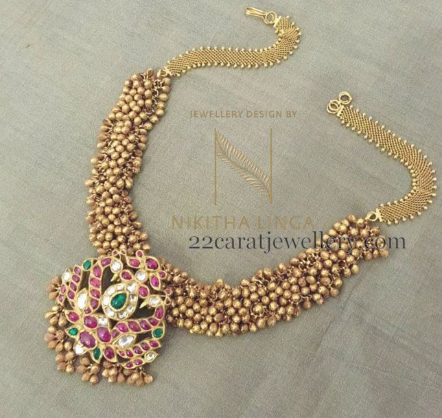 Small gold swirls or Muvvalu embellished fusion work very pretty gold necklace by Nikitha Linga . Temple style dual peacock pendant merged...