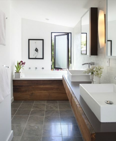 Stone tile floors, white vessel sinks, white bathroom with black  accents. Favorite is the natural wood siding on the counter top and bathtub. Would be the perfect bathroom if it had our Pop Down drains in the sinks. Visit bountybrassware.us for more details.