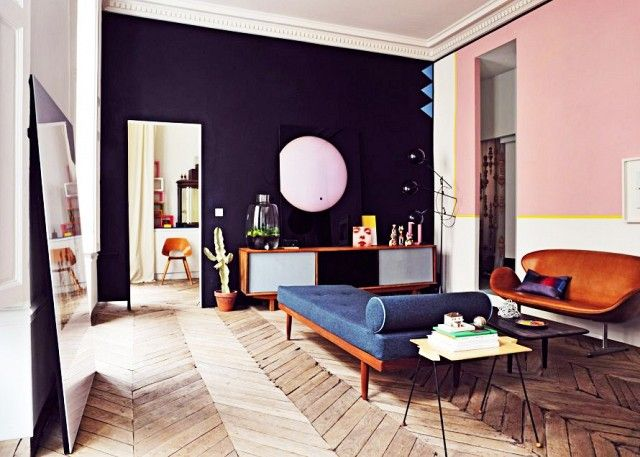 Retro-inspired living room with wood floors, colorful walls, and a mod daybed