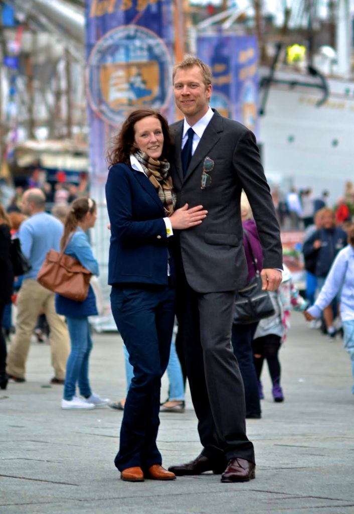 In Stavanger, Norway, at the Tall Ships Race, Ryan's outfit is 100% Budapest! He is wearing a bespoke charcoal-grey, fresco suit,  handmade shoes from Vass, and glasses by Tipton. Alette's scarf is pure cashmere tartan from our collection.