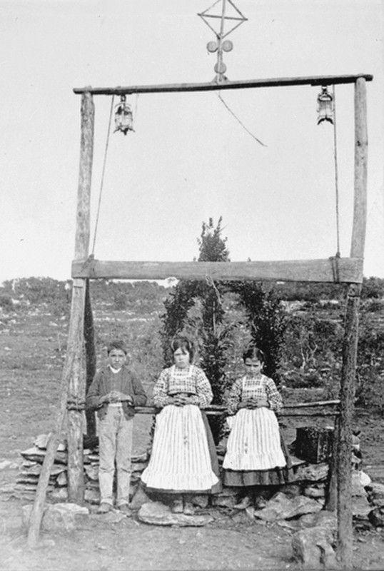 """I tre """"pastorinhos"""" Lúcia dos Santos (al centro) coi cugini Francisco e Jacinta Marto, sotto lo steccato innalzato dalla famiglia Carreira - detto """"l'arco"""" -, per marcare il luogo delle Apparizioni  (fotografia posteriore al 13 ottobre 1917)"""