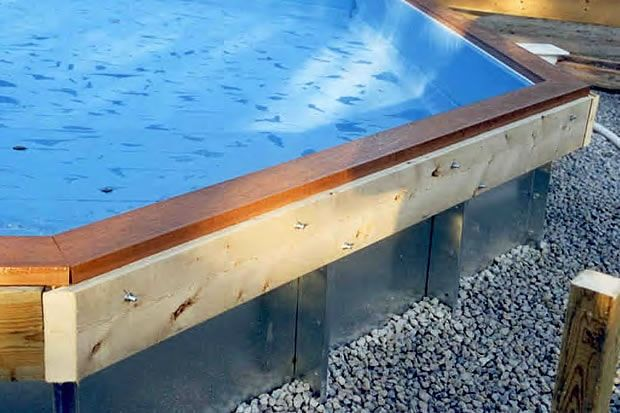 Ledger board bolted to the metal flange of an on-ground pool.