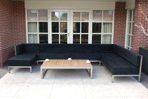 Terras meubilair op maat gemaakt voor in de nis, rvs met zwarte stof. Hoekbank met hocker.