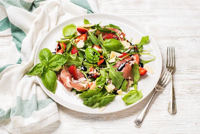 #Prosciutto and strawberry salad  Summer arugula prosciutto and strawberry salad over white painted wooden background selective focus