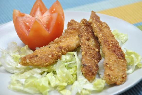 Pollo empanado en kikos o maíz frito. También incluye la receta para preparar kikos caseros--> Breaded Chicken Fingers.