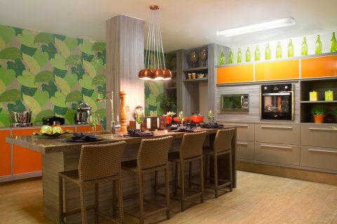 Cozinha. Durante a reforma desse espaço, as arquitetas Simone Moura e Fernanda Loyola descobriram um pilar oculto. Para não derrubá-lo, criaram uma bancada que serve como suporte para fogão, mesa e pia. Os vidros cor de laranja nos armários trazem cor ao ambiente – assim como o papel de parede com estampa de plantas. A cozinha tem 28 m².